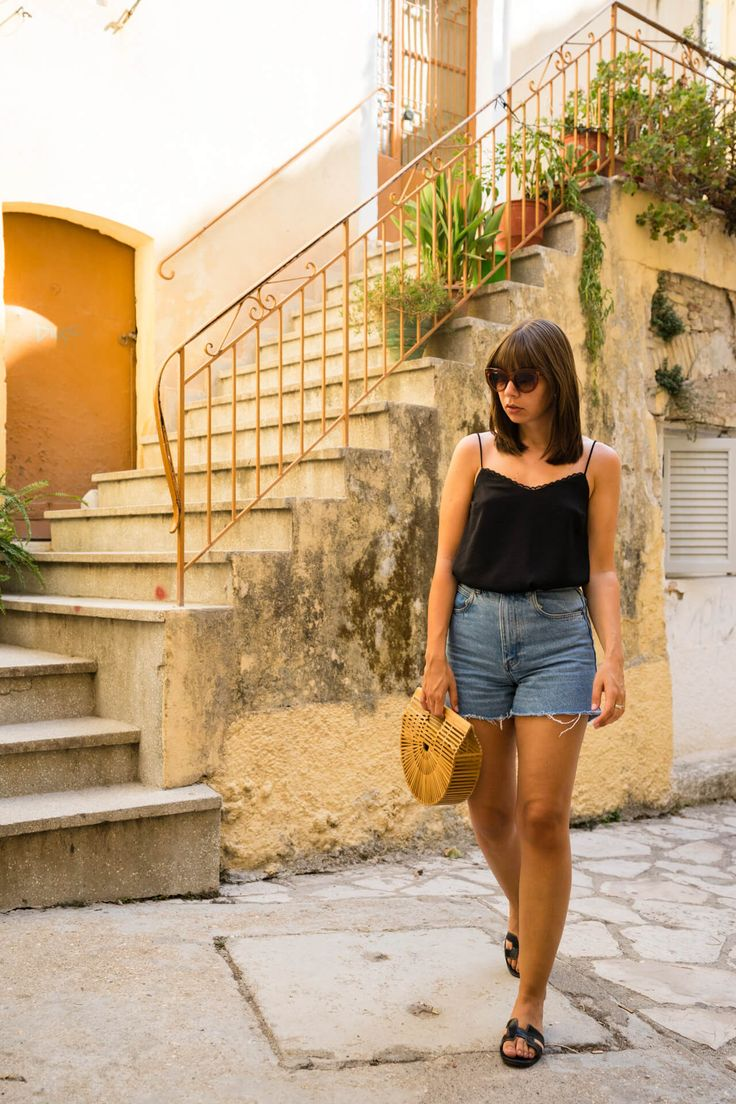 Leichter Urlaubslook mit Jeans Shorts, Camisole und Bambus Tasche. Das Sommer Outfit wird abgerundet von Hèrmes Oran Sandalen und Statement Sonnenbrille. Fotografiert in den Straßen von Kerkyra auf Korfu.