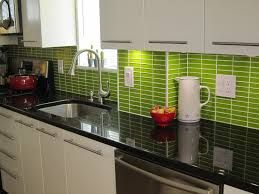 green mini tiles in vertical rows black quartz countertops