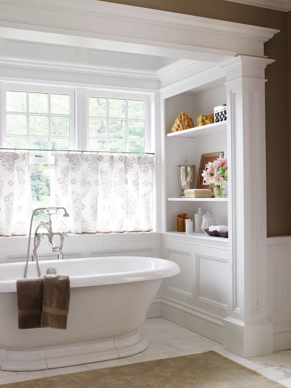 The master bath tub sits in a nook with views of a pond.  Heart of the Matter | New England Home - What about doing shelving at one end of the tub?