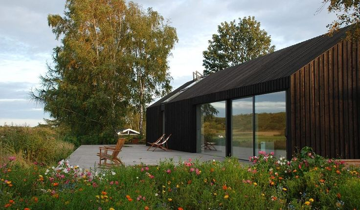 By Råbylille beach on the island of Møn, and some 350 m from the water's edge, stands the bright, spacious and attractively modern Black+Bright house. Pure