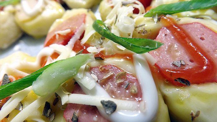 Roti topping sosis bertabur keju, bawang bombai, saos pedas dan mayones