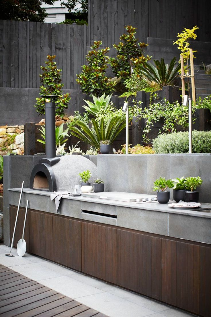 10 Awesome Outdoor BBQ Areas That Will Get You Inspired For Summer Grilling // This outdoor kitchen features hand polished stone and a pizza oven.