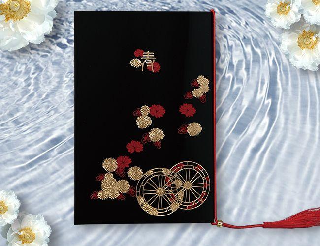 【留袖】結婚式に参加されるご婦人方の代表的な着物である「黒留袖」をイメージした招待状。光沢のある高級紙に、留袖の裾模様を何色もの特殊箔で贅沢に表現した豪華な仕上がり。赤の房リボンと金色の留めビーズが、一層カードのデザインを引き立てています。