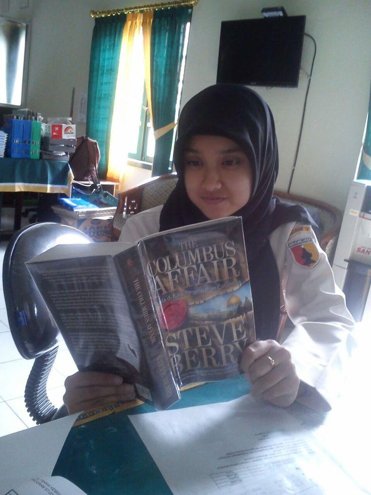 Mbak Sirli saat istirahat kerja di Poltekkes Soepraoen meluangkan waktu dengan membaca buku
