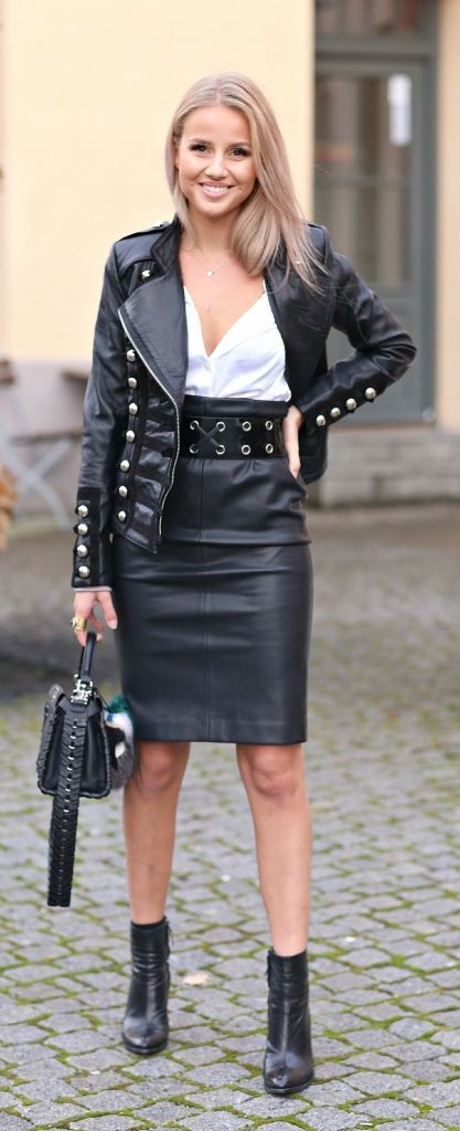 Black military style leather jacket, belted black leather skirt, ankle boots.