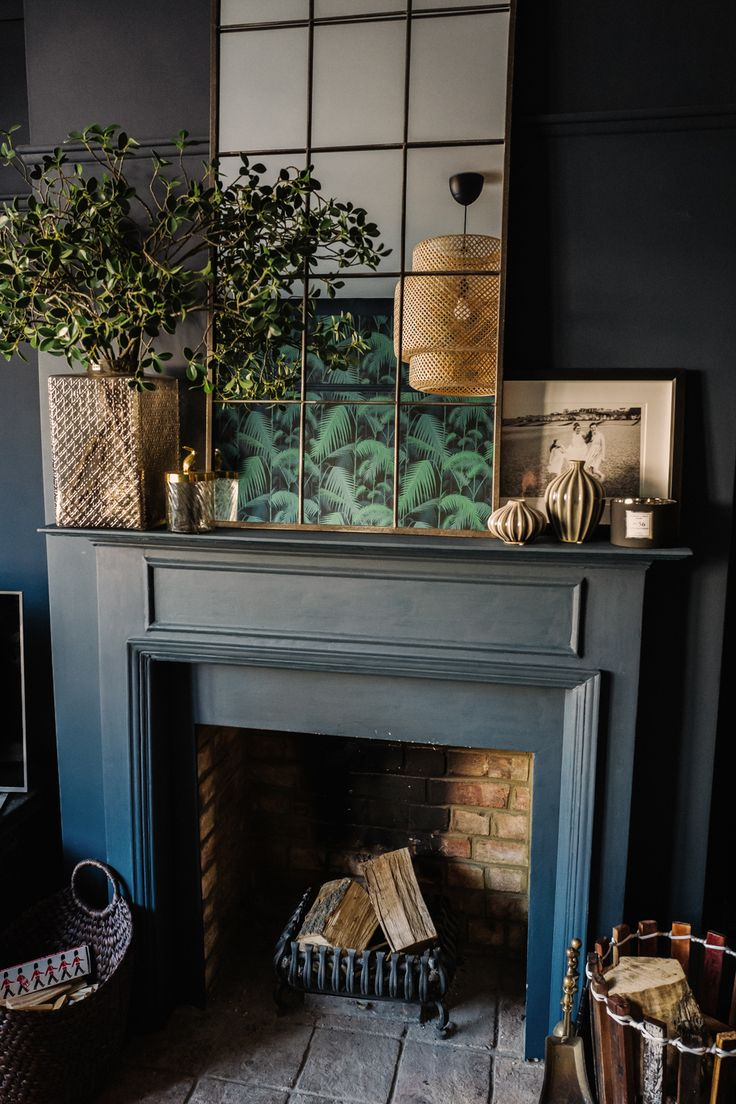 A gorgeous dark and moody, eclectic and glamorous living room design from Fiona Duke interiors with lovely copper framed mirror, and great fireplace styling.