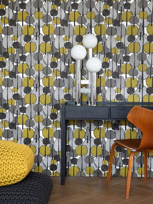 Into the Woods A pop of yellow adds a much-needed flair to this wallpaper of mixed grays, and the forest design is a contemporary alternative to the mural wall portraits popularized in the '70s. Image courtesy of Ferm Living Shop Advertisement