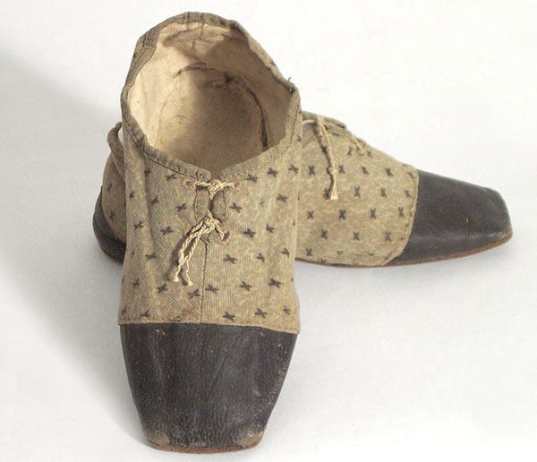Child's cloth shoes, c.1830    I love the printed cotton with its tiny Xs and vermicular background! These shoes are in remarkably good condition for such an important historical artifact.    The heels and toes are foxed with black leather, and the upper edges are bound with folded ribbon. The hand-stitched shoes close in front with ties. The rounded leather soles are straights and are heelless.