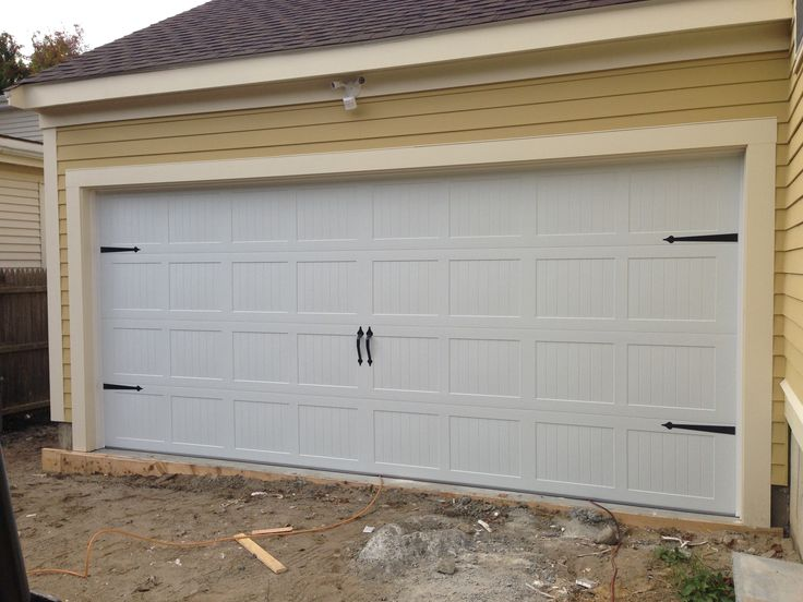 @C.H.I. Overhead Doors model 5283 Steel Carriage House Style Garage Door in  White with Flat Black Spade Decorative Hardware.