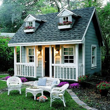 A pretty paved walk leads to this classic playhouse, made all the more endearing with sweet details such as turned porch railings, matching window boxes, and gabled dormers./