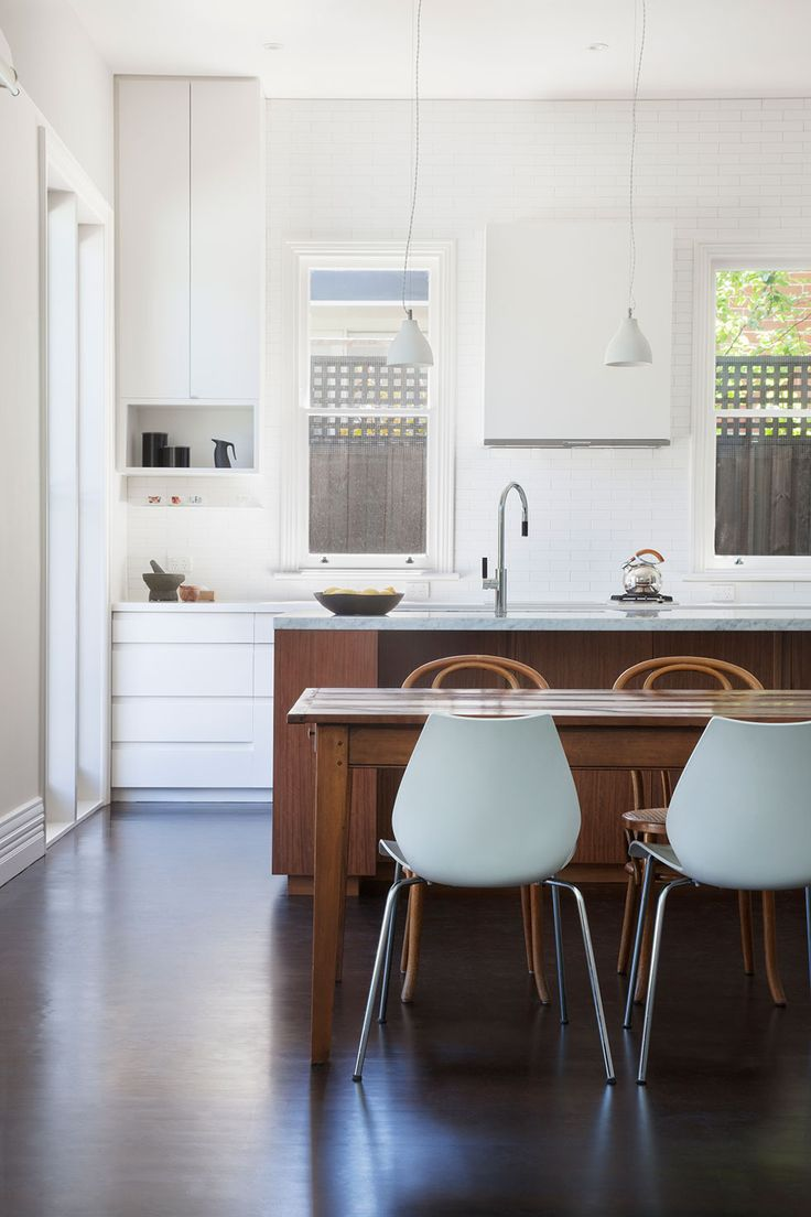 Kitchen island bench featuring a Carrara stone benchtop with grey ironbark veneer finish. Remainder of kitchen featuring matte finish cameo white corian benchtops and two pack paint to kitchen joinery. Matte white pressed edge ceramic tile as splashback and recycled Baltic pine timber floor | Glenderg Grove by Mihaly Slocombe (2015) | Malvern, Victoria, Australia | photo: Tatjana Plitt
