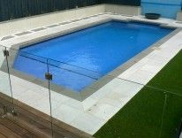 #White #Granite Paving used around a pool area. Offset with Bluestone Pool Coping Tiles to create a contrast between the coping and paving