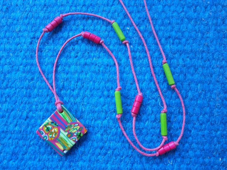 Zrcadlení Náhrdelník - kosočtverec z fimo hmoty s proužky ve veselých barvách, doplněn zelenými a růžovými dřevěnými korálky.  Rubová strana je barevná - proužky proložené kolečky. Náhrdelník lze nosit otočen na lícovou nebo rubovou stranu.  Navlečeno na voskové šňůrce bez zapínání. Délka šňůrky je 38 cm, kosočtverec má stranu o délce 2,5 cm.