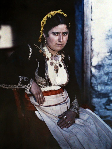 A woman sits in a chair in Anogia, the presumed home of the God Zeus, Crete; 1920's; Images by Maynard Owen Williams / Wilhelm Tobien;  Source: National Geographic Stock