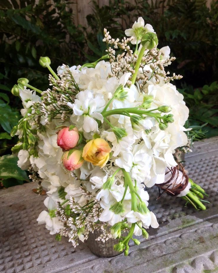 Bridesmaids bouquet of white hydrangea, baby's breath, white stock, highlighted by peach ranunculus buds.