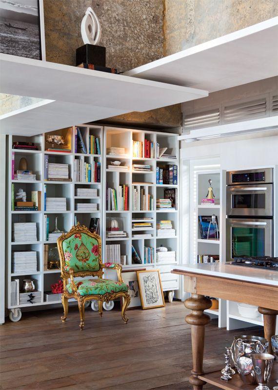 Lado a lado, as estantes com rodízios aproveitam a parede. A poltrona Luís 15 foi modernizada pelo tecido estampado. Mesa de pés torneados produzida por Geraldo Argeu.
