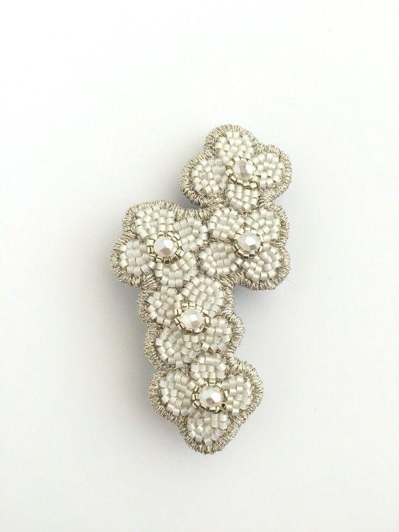 ビーズ刺繍ブローチです。白いビーズの周りに銀色の刺繡糸でステッチしています。花の中心にホワイトパールの大きめのビーズを使っていて存在感があります。白、銀の同系色なので、合わせやすいです。ブローチの重さ5グラム程度ですので、色々なものにつけやすいと思います。カーディガン、ストール、トートバッグなどにいかがでしょうか。☆りぼんをつけた簡単なラッピングをしています。<素材>ビーズ、刺繍糸、フェルト、ブローチピン(3センチ)<サイズ>タテ約7cm×ヨコ約3.5cm(一番幅の広い部分)一つ一つ手作業のために、表情がそれぞれ異なる場合がございます。ご理解いただける方にご購入をおすすめしております。PC環境設定などにより、画像と実物の色合いに差がある場合があります。返品、交換はご遠慮願います。発送は定型郵便です。追跡及び、紛失などの補償は出来ませんのでご了承下さい。土日祝日は、発送していません。