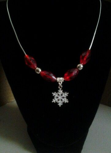 Small snowflake with red beads and silver beads on a silver cord