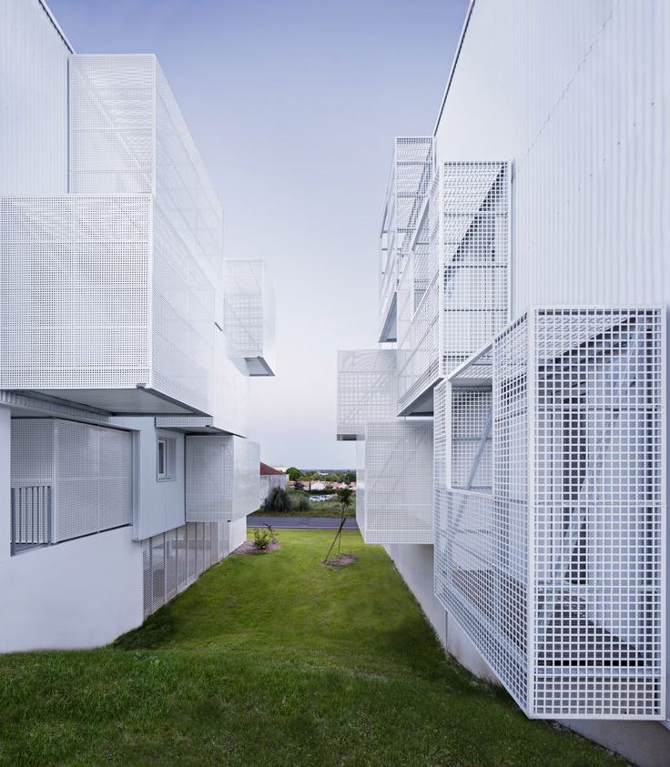 White caged balconies project from the sides of this social housing block by French collective Poggi + More