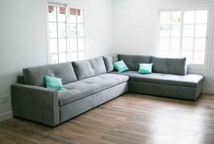 A sala da casa de Bruna Vieira. Sofá cinza mescla planejado e piso laminado.