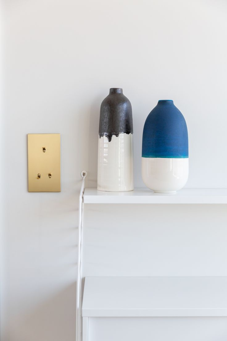Brass light switch and string shelving with dip dyed vases in apartment designed by Studio Mills