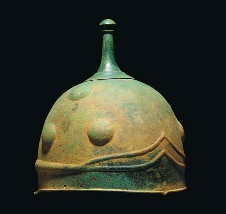 Celtic helmet, 3th-2nd century B.C. Of domed form with raised circular apex surmounted by knopped finial, a raised triangular plate with three repoussé bosses on each side, with horizontal tapered rib at the rear, 21.6 cm high. Private collection, from Christie's auction