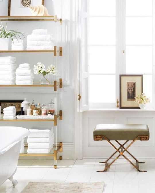 Lucite and brass shelving unit in the bathroom - all white with a X bench in brass and olive and large windows with roll top bath. Gorgeous!