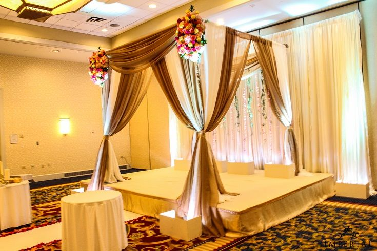Elegant Wedding Mandap with Gold and white fabrics draped with Fresh flower accents of Red, Yellow and Orange Roses and garlands draping in the back.