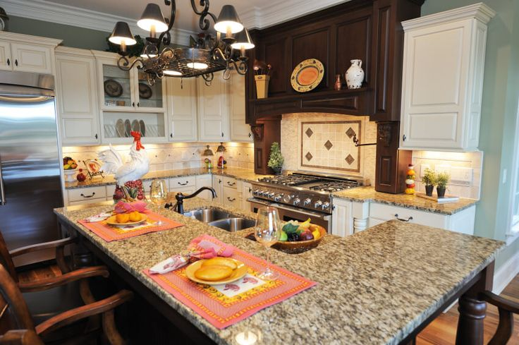 Compact, richly detailed kitchen holds this two-tiered island with built-in sink and raised dining surface of light marble.