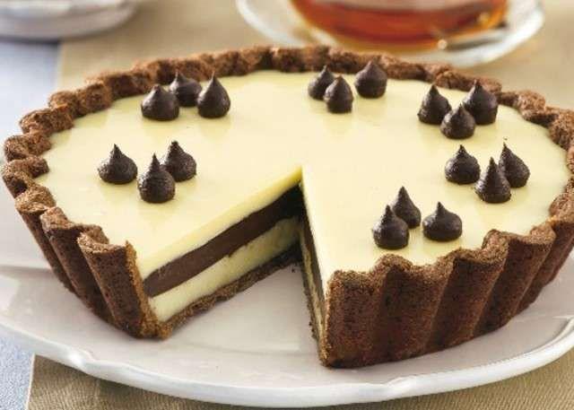 La torta al doppio cioccolato è la ricetta di un delizioso dolce da gustare come merenda o a fine pasto. La base della torta è realizzata con della semplice pasta frolla che poi dovrà essere farcita con due strati di ganache al cioccolato bianco e un strato intermedio realizzato con la ganache al cioccolato fondente. Per la base della torta potete anche preparare un pan di Spagna classico oppure al cacao. In questo modo, potete ottenere una golosa variante della ricetta!