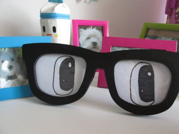 Fun and quirky Nerdy Glasses Frame with eyes. They instantly add fun to any place, be it your office, living room or your optician practice (if you have one).  Firstly, Do you know why my phone wears glasses? Read on to find out!  The frame has a strong cardboard leg for propping it up as well as 2 hooks on the back of the frame should you prefer to have your glasses hung up on the wall. The cardboard backing is held securely in place by 7 clips. The frame measures 13 inches long  The eyes…