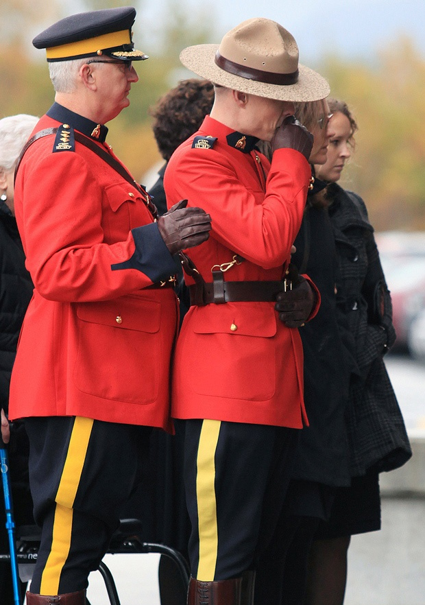 RCMP Const. Ben Oliver wipes away a tear during the funeral for his twin brother Const. Adrian Oliver as father Chief Supt. Joe Oliver stands with him in Langley, on Tuesday, Nov. 20. Adrian was killed on shift after being involved in a motor vehicle accident.