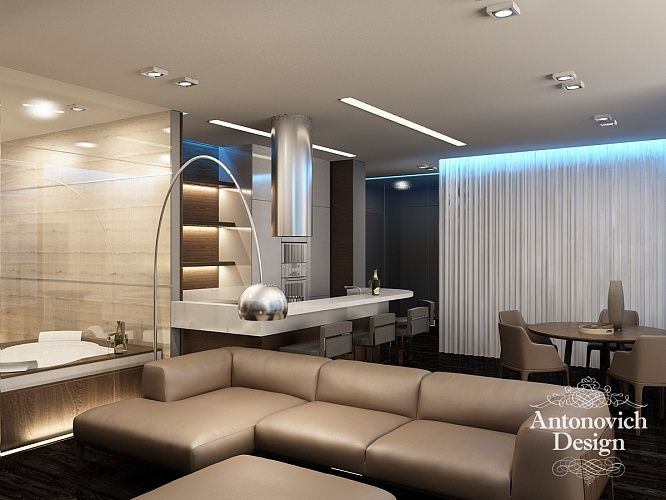 Мягкий диван в гостиной обит натуральной кожей, а снаружи отделан полосой тонкого шпонированного дерева.
