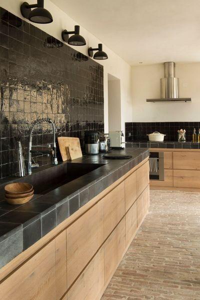 Suelo de cocina con ladrillo de caravista. Estilo clásico, acompañado con toques modernos en los módulos de madera natural. Bancada realizada con azulejo color negro grafito.