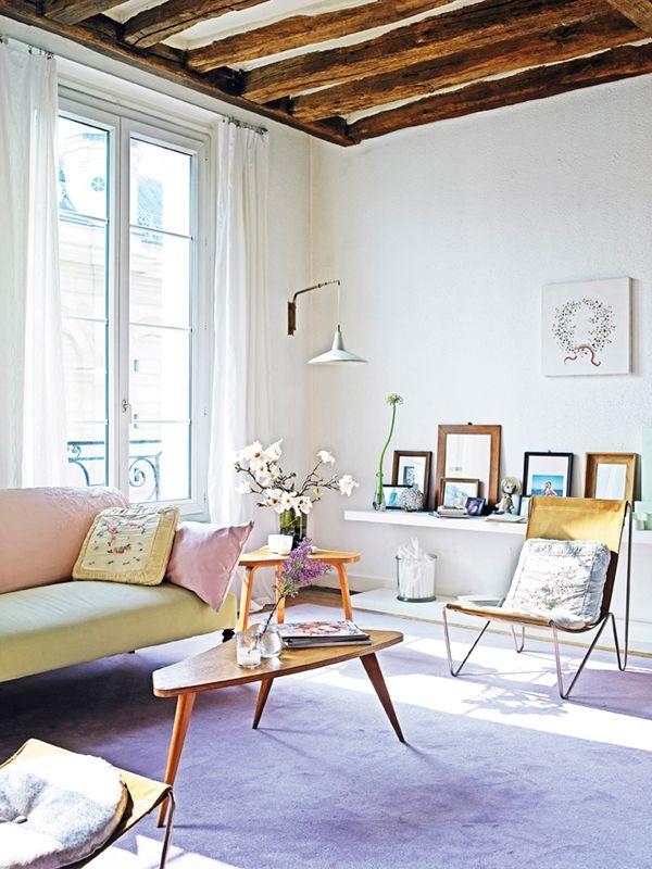 Den gamle sofaen fra ca. 1910 er blitt trukket om med et lysegrønt bomullsstoff. Over sofaens rygg ligger et stort rosa, brodert kinesisk sjal. En nydelig fargekombinasjon av rosa og mandelgrønt. På hyllene bak står det nye og gamle rammer med familiebilder, og forrest ligger noen små notisbøker med reisebeskrivelser. Den buede, grønne stilken på blomsten allium står i fin kontrast til rammene.