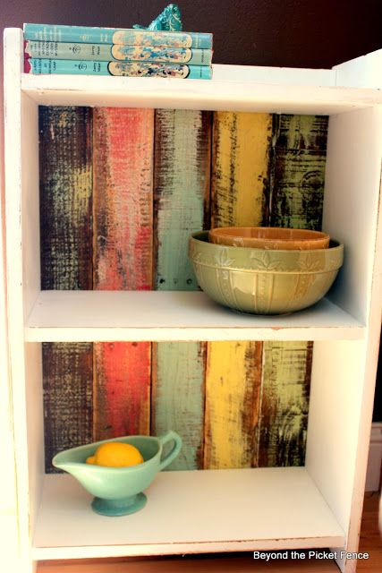 A clever and easy way to spruce up an old cupboard by simply nailing painted pallet pieces   as a new backing board.