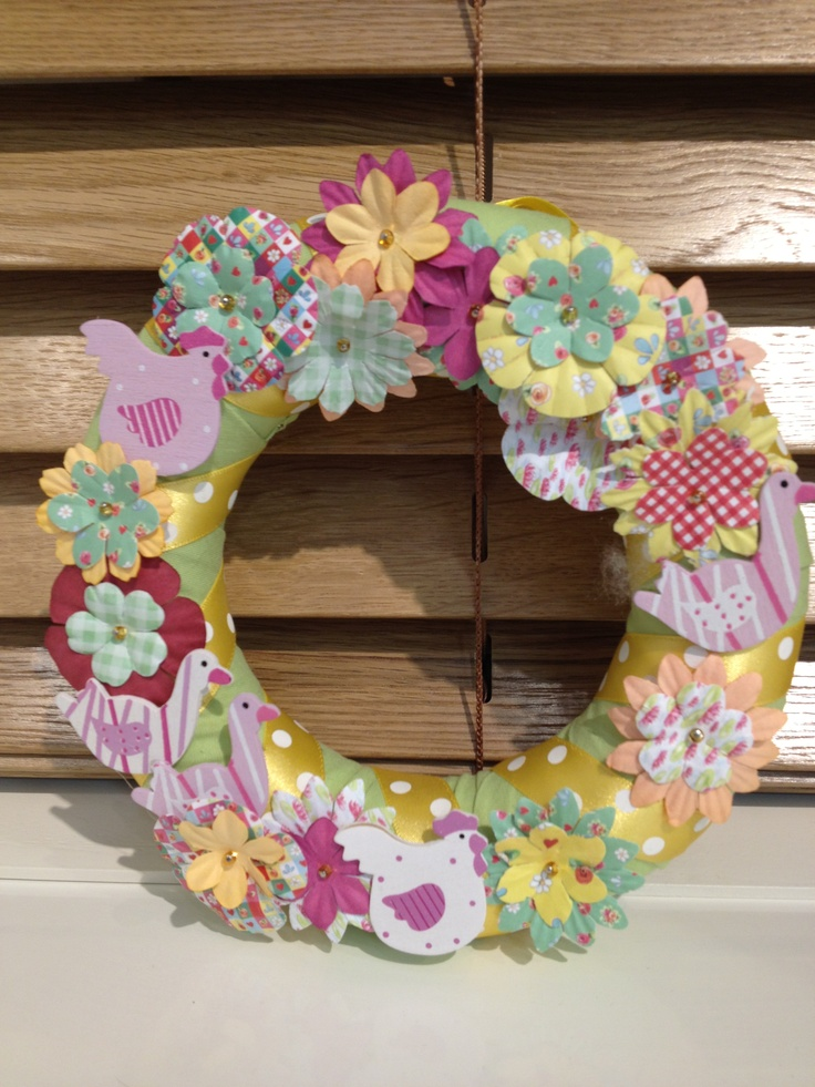 Polystyrene wreath wrapped with fabric and ribbon, with pinned paper flowers.
