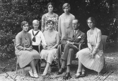 A young Prince Philip stands to the right of his mother, Princess Andrew (Alice of Battenberg) and Prince Andrew of Greece and Denmark (called Andrea). From left to right are Philip's sisters, all Princesses of Greece & Denmark: Margarita, Theodora, Sophie, and Cecilie (ca. 1930).