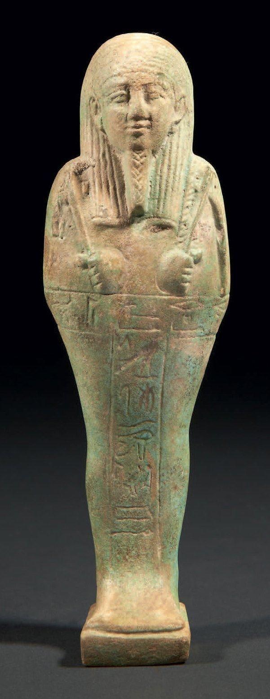 """OUSHEBTI AU NOM DU GÉNÉRAL HOR. Il est momiforme, coiffé de la perruque tripartite striée, paré de la barbe postiche, et tient les instruments aratoires. Les jambes sont gravées d'une inscription hiéroglyphique en T: """"Que soit illuminé l'Osiris, le prince héréditaire, le prêtre et général Hor, né de Oudjachou, juste de voix."""" Faïence siliceuse à glaçure verte. Égypte, Basse Époque, XXXe dynastie."""