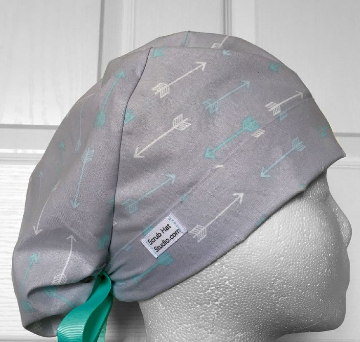 Sweet gray cotton tie back hat with white, mint green, and light blue arrows. Has an elastic backing for a ponytail, a front folding band that flips up for an adjusted fit, and matching ribbon ties.