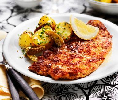 Hemlagad panerad kyckling, med en läcker krispig yta, serveras med smarrig potatissallad med smak av senap, vinäger, honung, gräslök och cornichoner. Servera den delikata kycklingen tillsammans med potatissalladen, en klick gräddfil och syrlig citronklyfta.