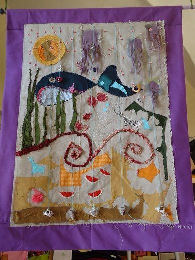 Pannello in tessuto e conchiglie. Opera di Francesca Nikki