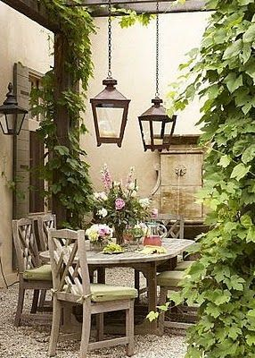 Cozy outdoor dining area beneath a lush, icy-covered pergola with hanging iron lanterns.