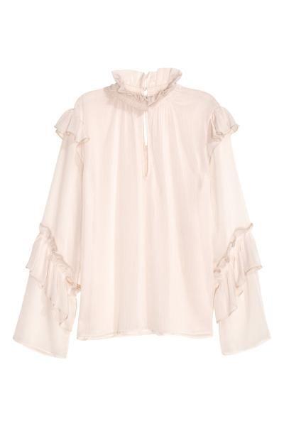 Blusa con volantes: H&M. Blusa en tejido doble con efecto arrugado. Modelo con cuello elevado y fruncido con volante, abertura delante y detrás, botones revestidos en la nuca, y volantes en los hombros y en las mangas.