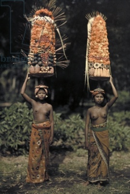 Two Balinese women carry temple offerings of fruit on their heads, Bali, Indonesia, 1928