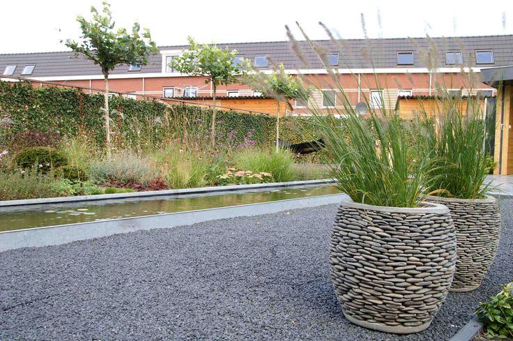 Plantenbak kiezelsteen gevuld met miscanthus. Ontwerp en aanleg hoveniersbedrijf van Elsäcker Tuin