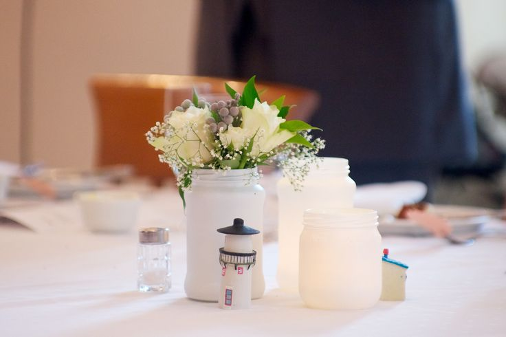 Table decorations The minihouses are from Kardemomme by/ Cardamom Town, a city based on Thorbjørn Egners story- both of us have worked in the city so it is a part of our story.   Jam jar for lights and flowers, sprayed with white paint.