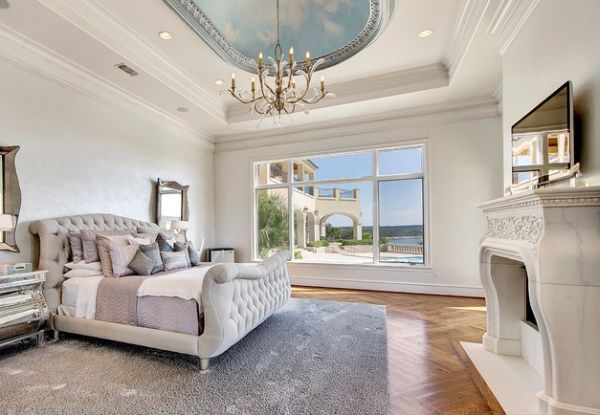 Carved marble fireplace and tufted sleigh bed bring opulence to the bedroom