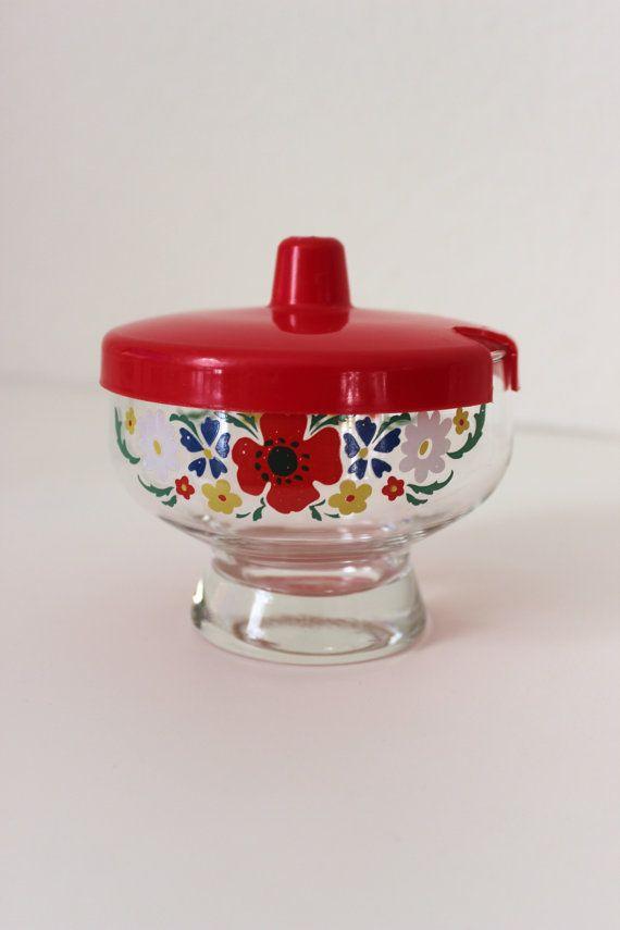 Zuckersüßes, seltenes Set für den Frühstückstisch, bestehend aus - 2 Salzstreuern - Zuckerstreuer - Marmeladen/ Honigglas  Das Geschirr stammt aus den 70er Jahren. Die Gefäße sind aus Glas mit einem einheitlichen Blumendekor. Die Deckel sind jeweils aus Kunststoff.  Sehr guter Vintagezustand. Der rote Deckel des einen Salzstreuers hat einen Riss, sitzt aber noch fest auf dem Glas (s. Foto)  Maße: Salzstreuer: Höhe: 7 cm | 2,75 inch Zuckerstreuer: Höhe: 10 cm | 3.93 inch Marmeladenglas: ...