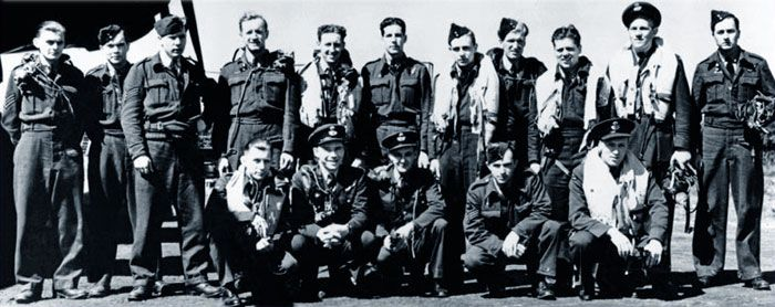 "This photo shows 16 of the 17 RCAF personnel who survived the Dambusters raid. Standing, left to right: Sergeant Steve Onancia, Sergeant Fred ""Doc"" Sutherland, Sergeant Harry O'Brien, Flight Sergeant Ken Brown, Flight Sergeant Harvey Weeks, Flight Sergeant John William ""Jack"" Thrasher, Pilot Officer George A. Deering, Sergeant William G. Radcliffe, Flight Sergeant Donald A. MacLean, Flight Lieutenant Joseph C. McCarthy and Flight Sergeant Grant S. MacDonald, air gunner, F-Freddie. Kneeling…"